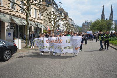 Schülerinnen und Schüler laufen auf einer Straße mit einem Transparent vor sich her. Dahinter eine große Menge weiterer Schülerinnen und Schüler mit weiteren Transparenten und Schildern.